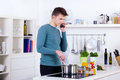 Young man cooking meal talking phone his kitchen Stock Images