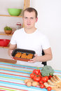 Young man cooking meat in the kitchen Royalty Free Stock Photo