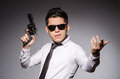 Young man in cool sunglasses holding gun Royalty Free Stock Photo