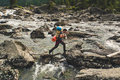 Young man crossing mountain river. Royalty Free Stock Photo