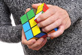 Young man and cube puzzle a trying to solve a rubiks this famous was invented by the architect erno rubik in Stock Image
