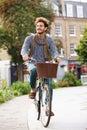Young Man Cycling Through Urba...