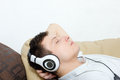 Young man daydreaming listening to music over headset Royalty Free Stock Photo