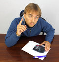 Young man at the desk with calculator Royalty Free Stock Photo