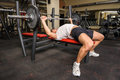 Young man doing bench press workout in gym Stock Image