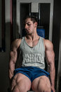 Young man doing heavy weight exercise for legs on machine leg extensions bodybuilder Stock Image