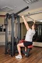 Young man doing lats pull down workout in gym handsome b Royalty Free Stock Photos