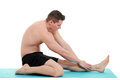 Young man doing leg stretch on white Royalty Free Stock Image