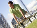 Young man doing press ups on bench outdoors smiling low angle view tilt Royalty Free Stock Photos