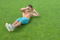 Young man doing sit-ups on green grass Stock Photo