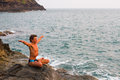 Young man doing yoga exercise on the sea beach deserted wild stone Stock Images