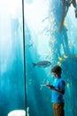 Young man drawing a fish in a tank illuminate at the aquarium Stock Photo