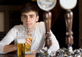 Young man drinking alone view between the beer taps on a dispenser of a serious at the counter in the bar or pub Royalty Free Stock Photos
