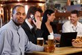 Young man drinking beer in pub men at with colleagues holding mug smiling Royalty Free Stock Photos
