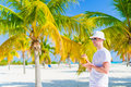 Young man drinking coconut milk on hot day on the beach in palm grove Royalty Free Stock Photo