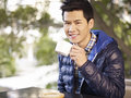 Young man drinking coffee asian adult smiling by the window Royalty Free Stock Photos