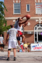 Young man drives to basket in outdoor street basketball tournament athens ga usa august a the with a defender on him a on held on Royalty Free Stock Photography