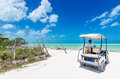Young man driving on a golf cart at tropical white sandy beach Royalty Free Stock Photo