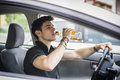 Young man driving his car while drinking alcohol Royalty Free Stock Photo