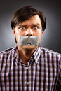 Young man with duct tape over his mouth against gray background conceptual image Stock Image
