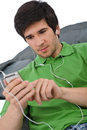 Young man with ear buds listening to music Stock Image