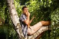 Young man eating apple on tree at summer Royalty Free Stock Photography