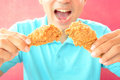 Young man eating deep fried chicken legs or drumsticks a with opening mouth about to eat Royalty Free Stock Photos