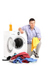 Young man emptying a washing machine isolated on white background Royalty Free Stock Image
