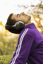 Young man enjoying listening to music in park Royalty Free Stock Photo