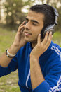 Young man enjoying listening to music in park Royalty Free Stock Photography