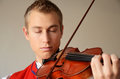 Young man enjoying playing violin Stock Photos