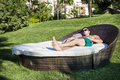 Young man  enjoying the summer vacation laying on sunbed in a tropical garden Royalty Free Stock Photo