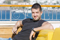 Young  man  enjoying the summer vacation sitting  on a sunbed on a sea background Royalty Free Stock Photo