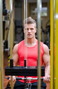 Young man exercising biceps on gym machine handsome in working out equipment Royalty Free Stock Images