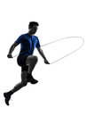 Young man exercising jumping rope silhouette one caucasian in studio on white background Stock Photography