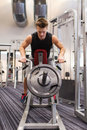 Young man exercising on t bar row machine in gym sport bodybuilding equipment and people concept with barbell flexing muscles Royalty Free Stock Images