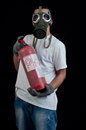 Young man extinguisher gas mask black background Stock Photography