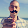 Young man with a fake moustache holding in stick in front of his face Stock Photography