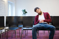 Young man falling asleep at conference room with beard in brown hoodie and blue jeans Royalty Free Stock Photo