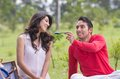 Young man feeding girlfriend at a picnic Royalty Free Stock Photo