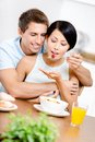 Young man feeds and hugs his girlfriend male sitting at the kitchen table concept of healthy dieting food Stock Image