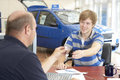 Young man filling in paperwork in car showroom Royalty Free Stock Photo