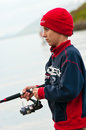 Young man fishing in norway holding pole and wearing red winter hat Royalty Free Stock Photos