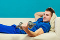 Young man fit body relaxing on couch after training relax sport activity or having dreams of muscular dumb bell in hand Stock Photography