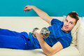 Young man fit body relaxing on couch after training relax sport activity or having dreams of muscular dumb bell in hand Royalty Free Stock Image