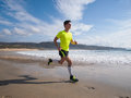 Young man in fitness clothing running along beach outdoors Royalty Free Stock Image