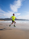 Young man in fitness clothing running along beach outdoors Stock Photo