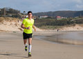 Young man in fitness clothing running along beach outdoors Royalty Free Stock Images