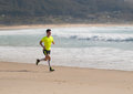 Young man in fitness clothing running along beach outdoors Royalty Free Stock Photography