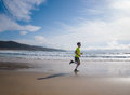 Young man in fitness clothing running along beach outdoors Stock Image